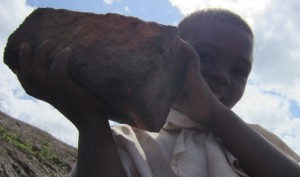 A boy helps in any way he can, by carrying a brick over to the construction site.