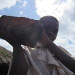 Un estudiante con un ladrillo de su escuela en el Congo