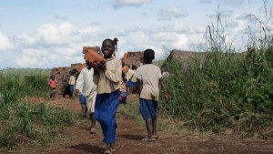 A school girl helping to carry bricks for her future new school